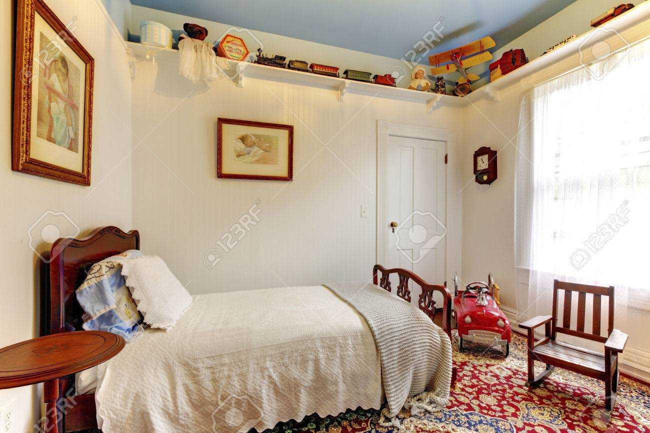 Bright White Boys Room With Wood Bed, Rocking Chair And Colouful Carpet.  Stock Photo