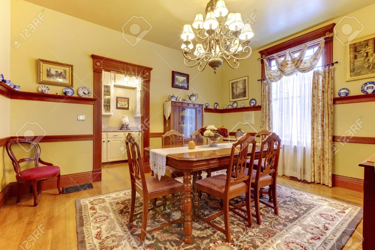 Lujoso comedor con juego de sillas mesa de madera, lámpara de araña y  colorida alfombra