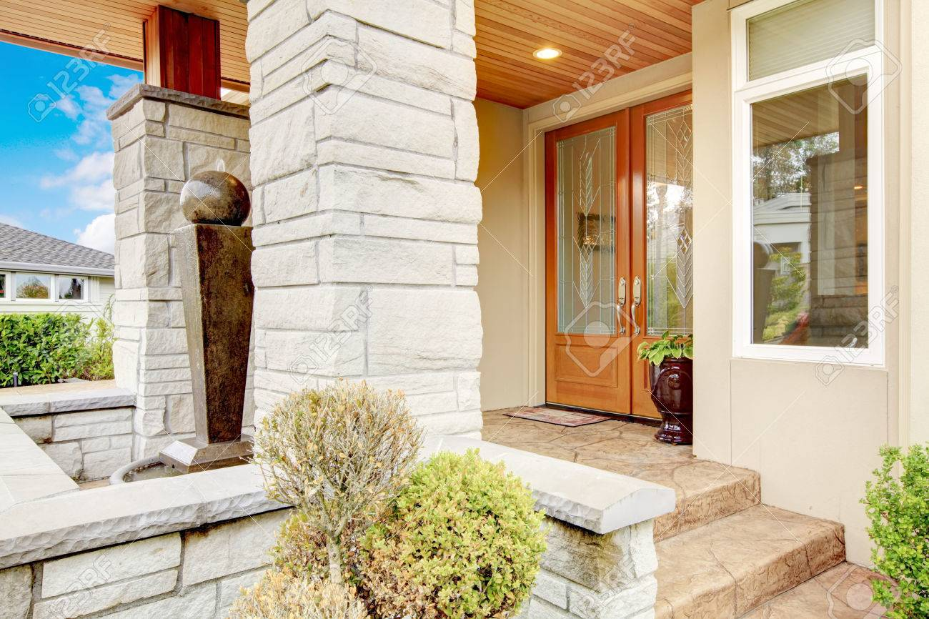 Luxury House Entrance Porch With Stone Column Trim, Stained Wood Door And  Window. Stock