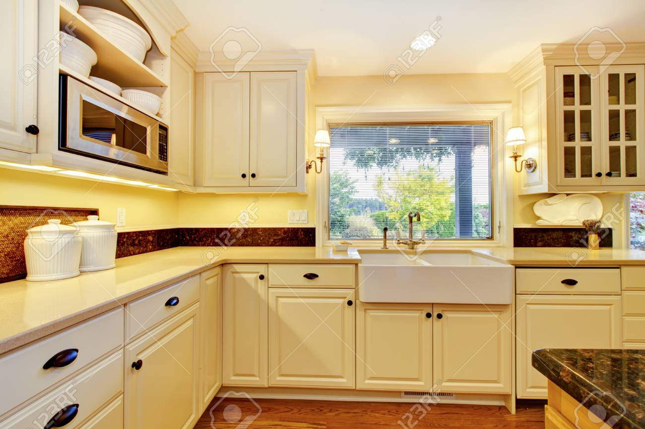 Crèmekleurige keuken met grote witte spoelbak en klassiek ontwerp