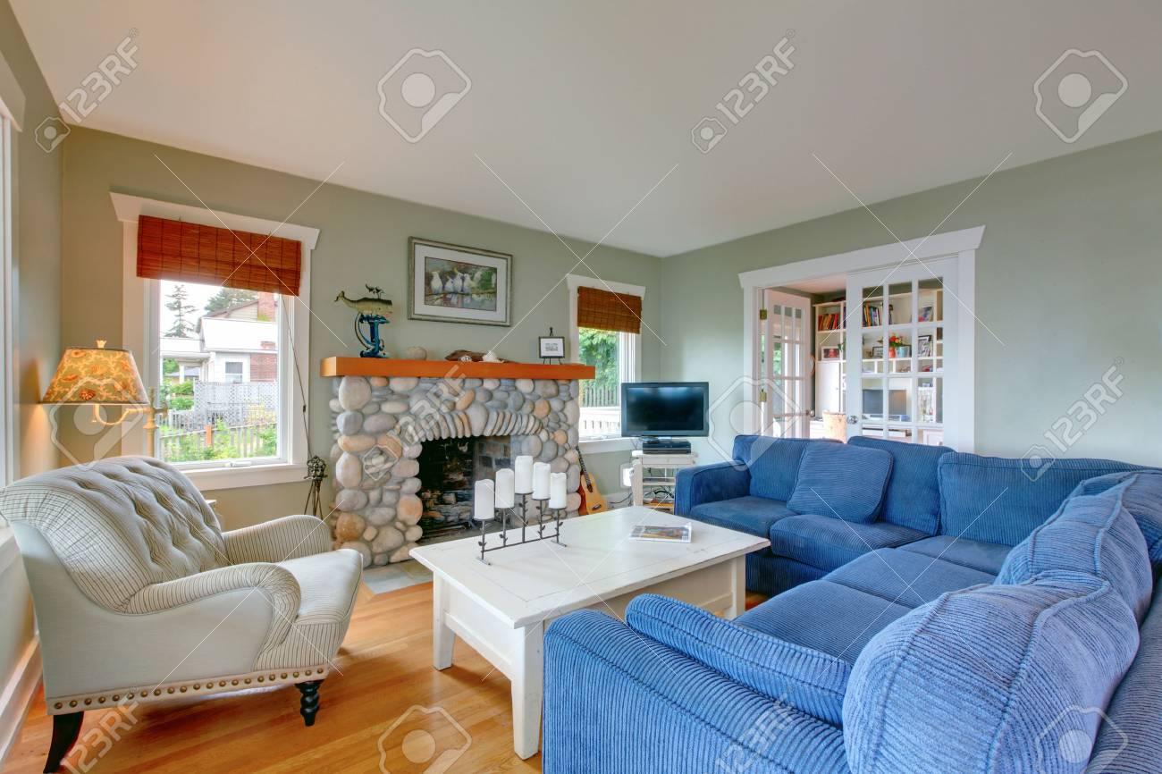 Salon américain classique avec canapé bleu confortable et cheminée décorée  de pierre.