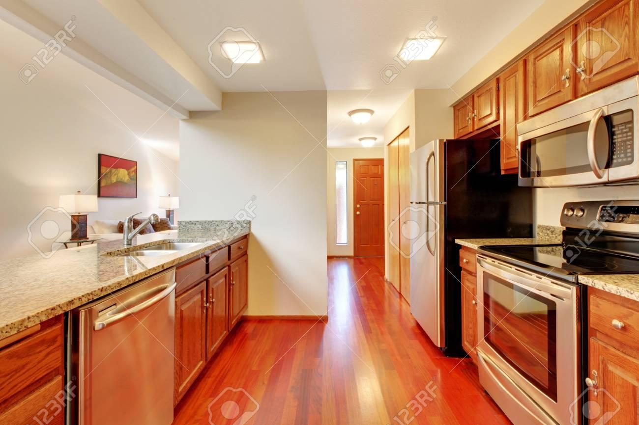 Cocina limpia, con muebles de madera y encimera de granito. Vista de  electrodomésticos de acero inoxidable.
