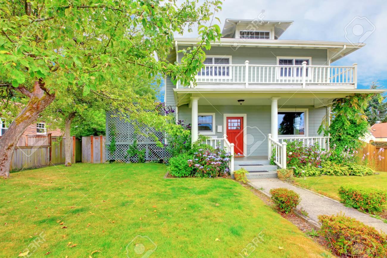 Jardin À L Américaine américaine vert à deux niveaux maison extérieur avec garniture blanche et  porte d'entrée rouge. porche confortable avec des colonnes blanches et des