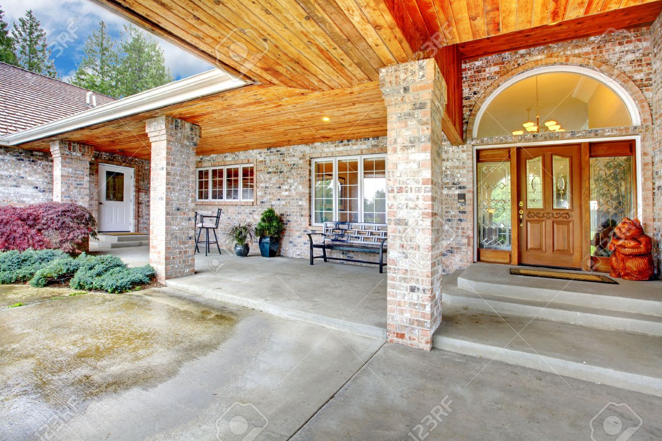Attractive Cozy Entrance Porch Of A Large Brick House. Patio Area With Concrete Floor  And Brick