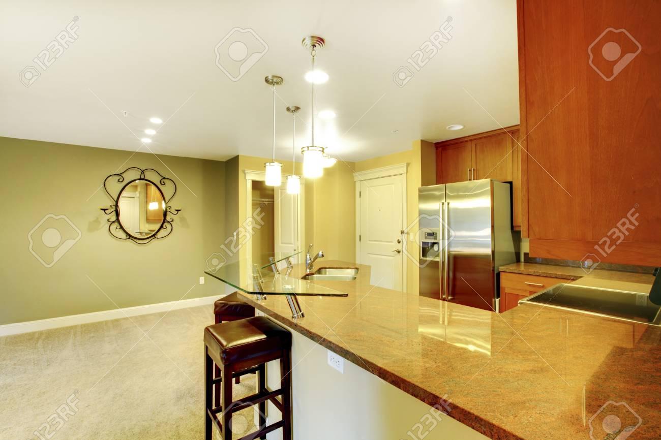 cocina interior brillante con encimera de granito, barra americana y