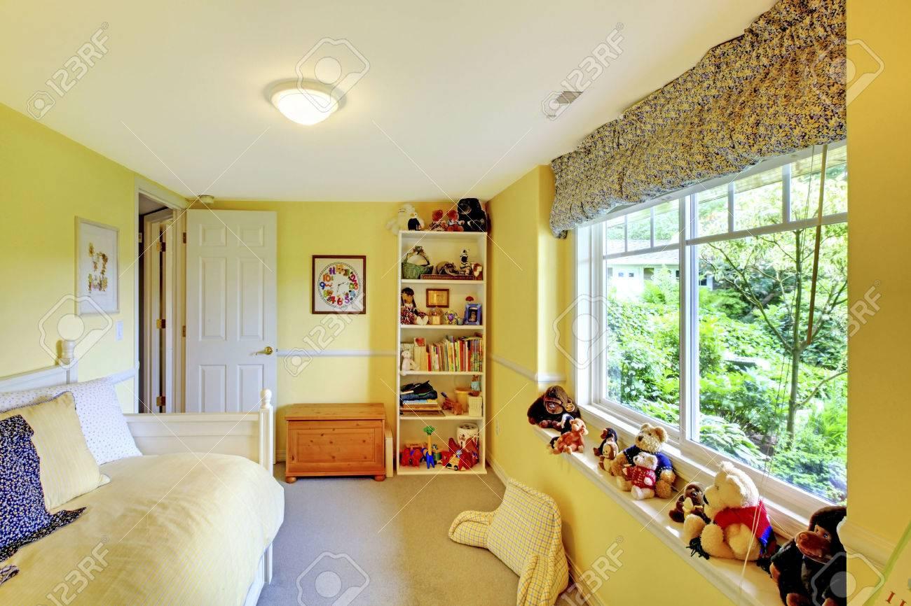 Kinder Spielen Ein Spielzimmer Mit Gelben Wänden, Beige Teppich Und Jede  Menge Spielzeug. Standard