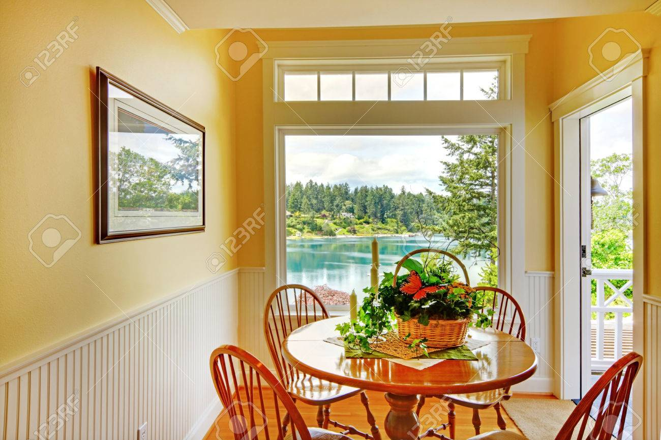 Comedor pequeño con paredes de color amarillo, tablón ajuste pared y mesa  redonda con sillas de edad. Habitación tiene salida a la terraza WalkOut