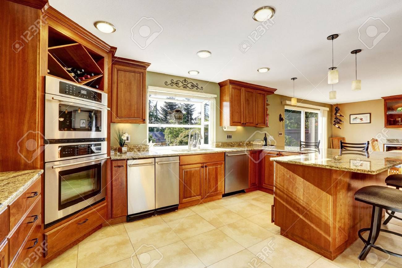 luxury kitchen with tile floor stained cabinets and granite