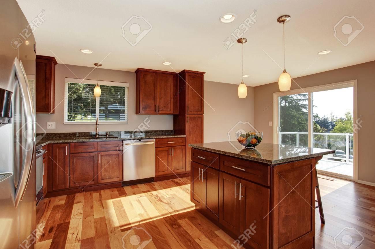 Spacieuse salle de cuisine avec bar, armoires marron et suspensions. La  chambre a des portes vitrées donnant sur le balcon.