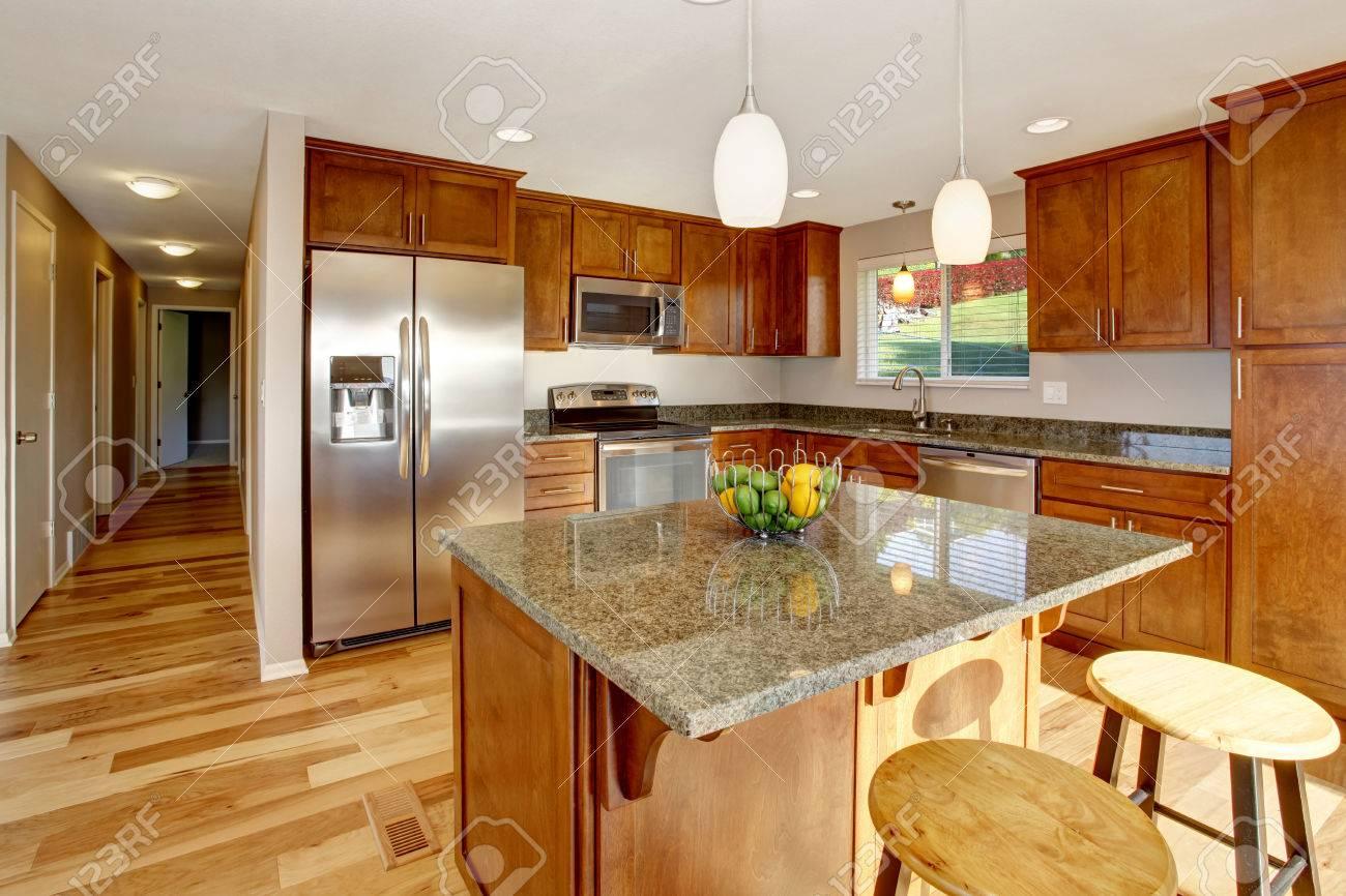 amplia cocina con barra americana, electrodomésticos de acero