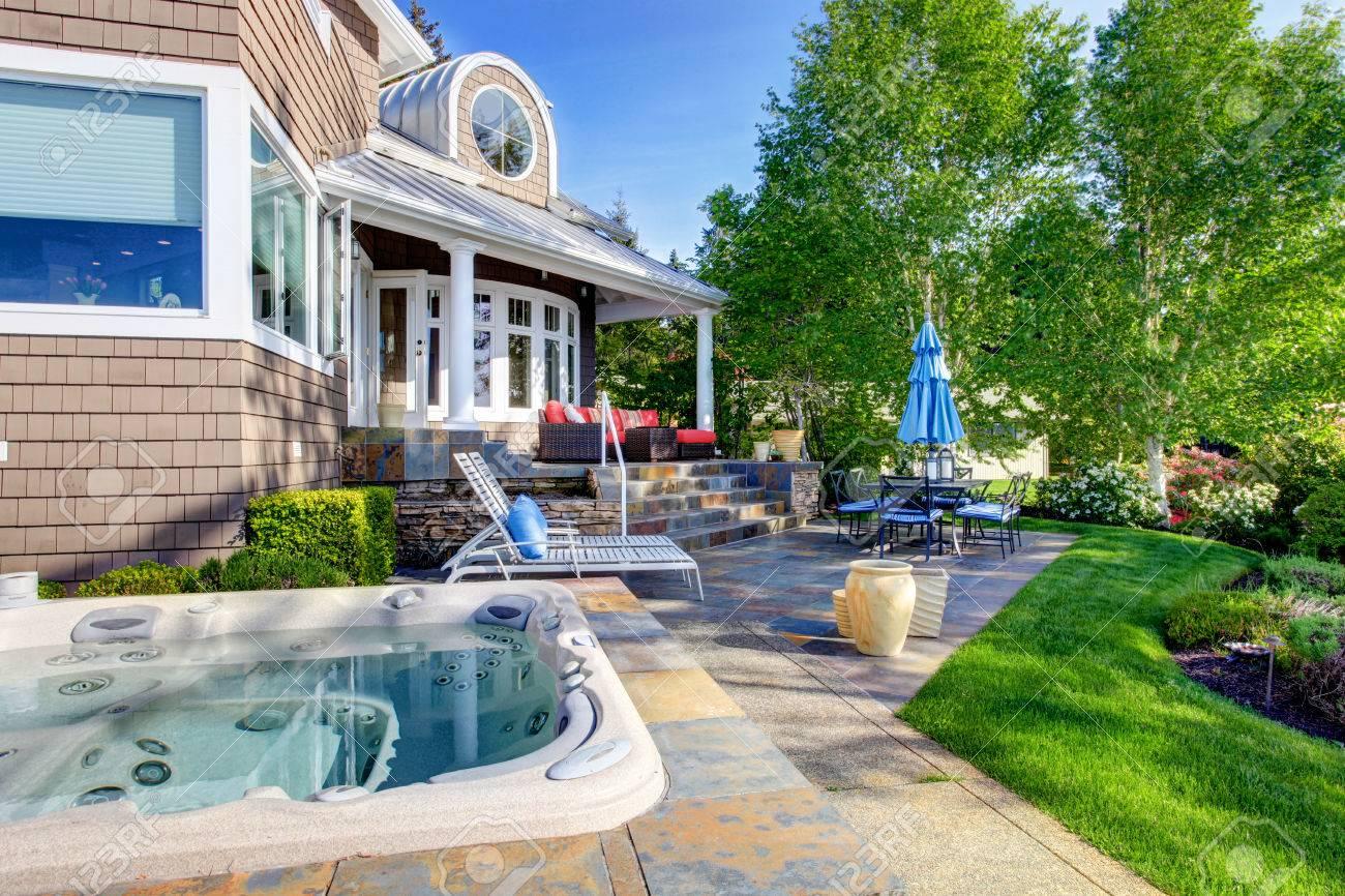 Maison de luxe extérieur avec un impressionnant design de jardin, terrasse  et un coin salon et un bain à remous.