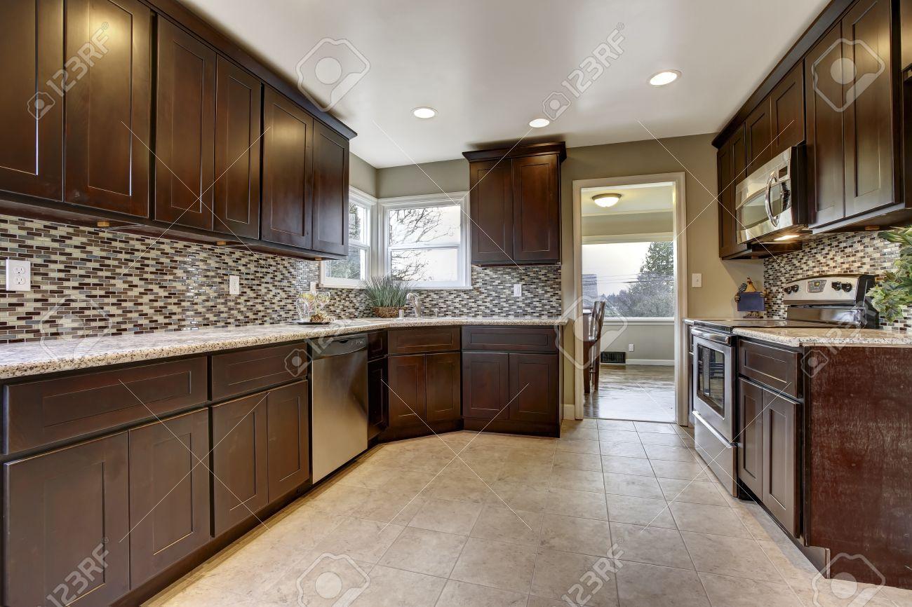 interior de la cocina moderna con armarios de color marrn oscuro con encimeras de granito y