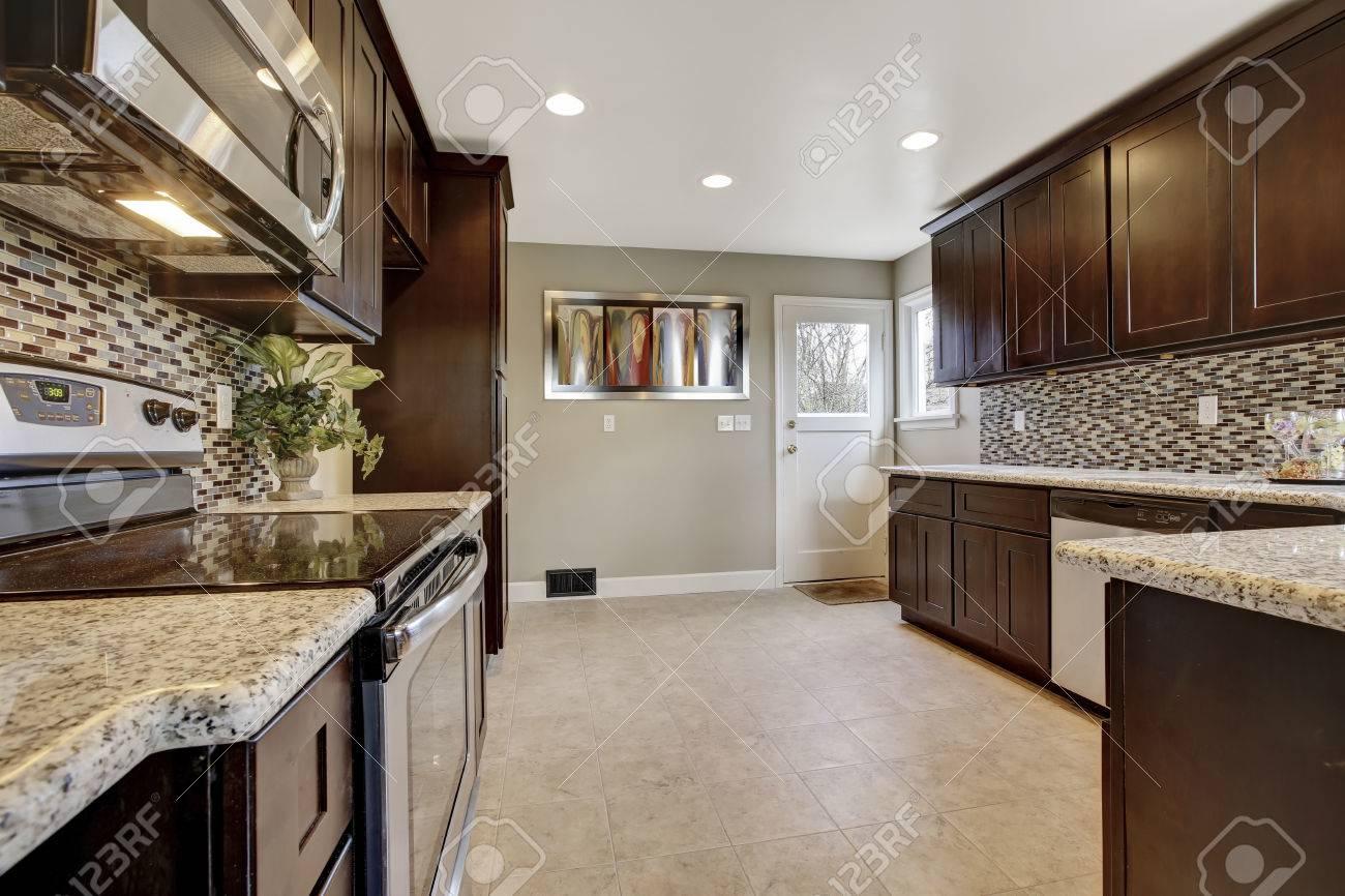 entre cocina moderna con armarios de color marrn oscuro con encimeras de granito y piso de
