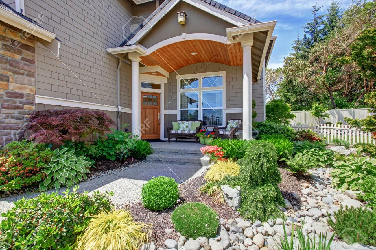 Extérieur maison avec terrasse en béton et aménagement paysager agréable