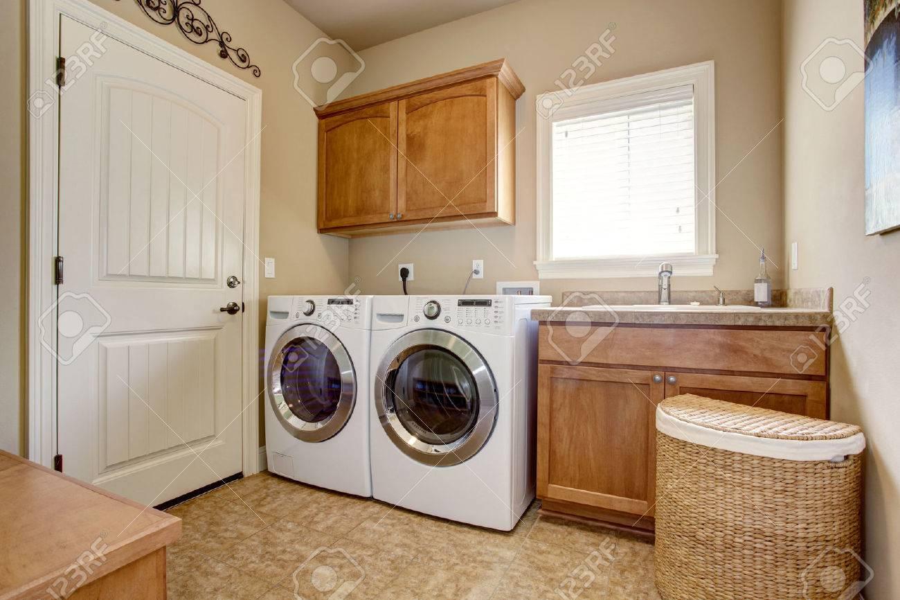 Waschküche mit waschmaschine und trockner. schränke aus holz und