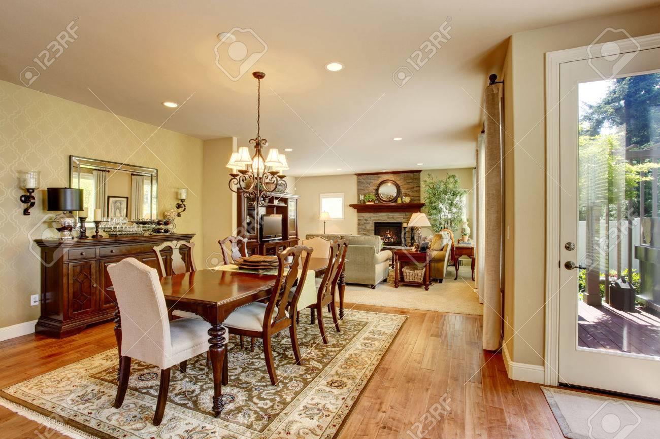 Comedor clásico americano con juego de mesa de madera, piso de madera y  alfombra. También conectado a la sala de estar