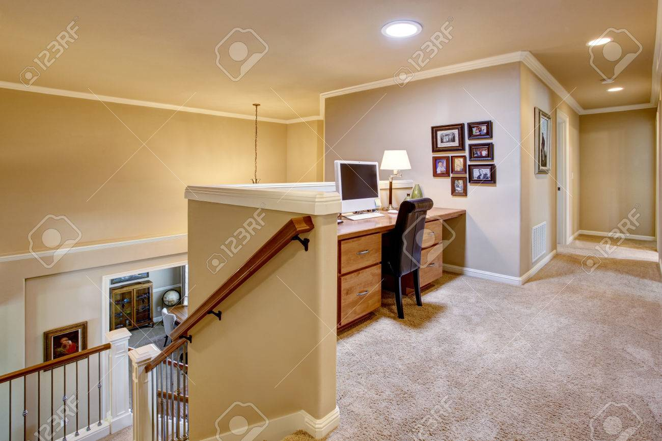 small home office area in the hallway with carpet floor. view