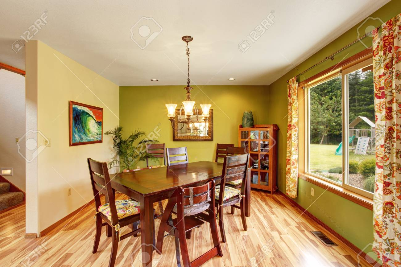 Antique Green Dining Room Interior With Mahogany Table Set And Chandelier.  Hardwood Floor And White