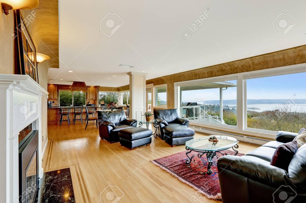 Schön Eingerichtetes Wohnzimmer Mit Parkettboden, Beige Wände Und Blick  Aufs Wasser Standard Bild