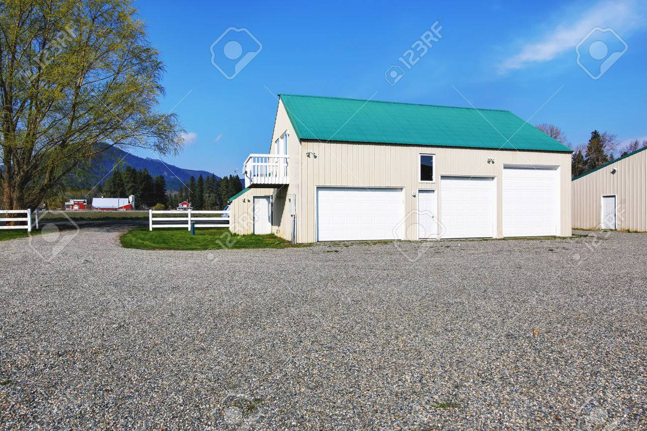 Separate Garage Building With Three Garage Doors And Gravel Driveway Around  Stock Photo   59955987
