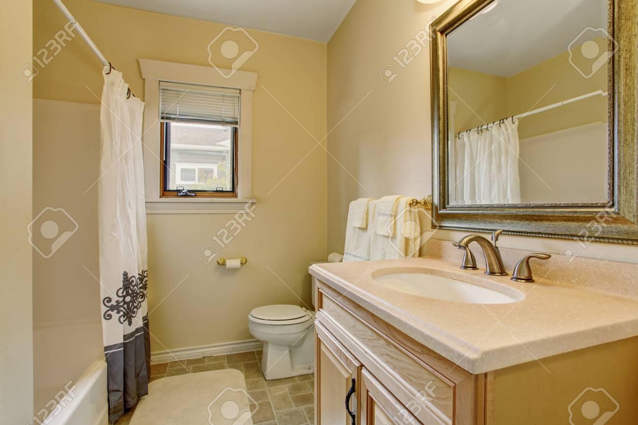 Warm Creamy Tones Bathroom Interior With Wooden Cabinet And Mirror