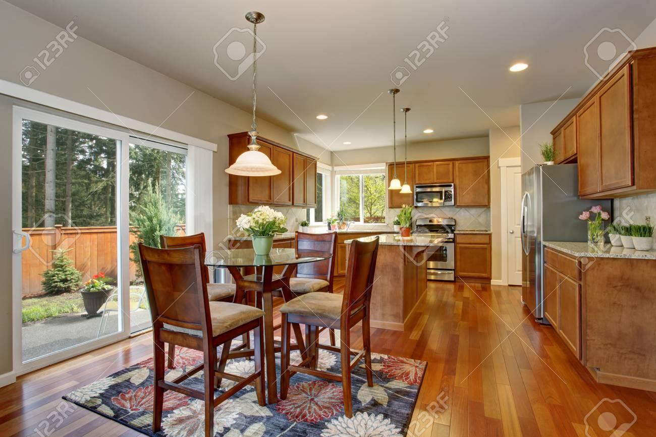 Cocina interior con piso de madera, muebles de color marrón y encimera de  granito. Conectado al comedor