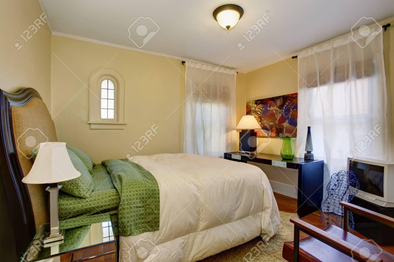 Petite chambre beige avec plancher de bois franc, literie blanche verte et  belle décoration.