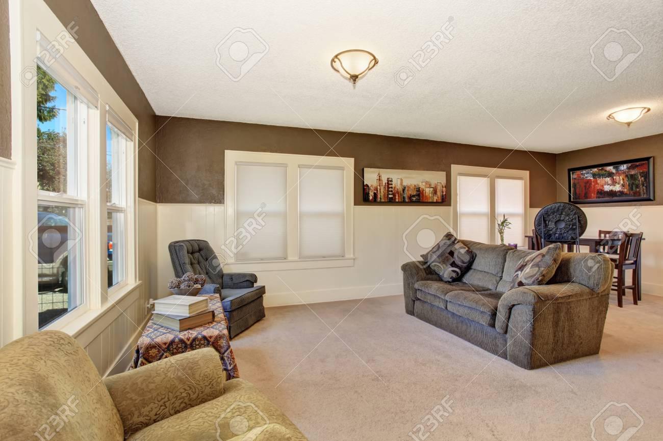 Blanc et brun salon inter avec un canapé confortable et la moquette beige.  Vue de la table à manger.