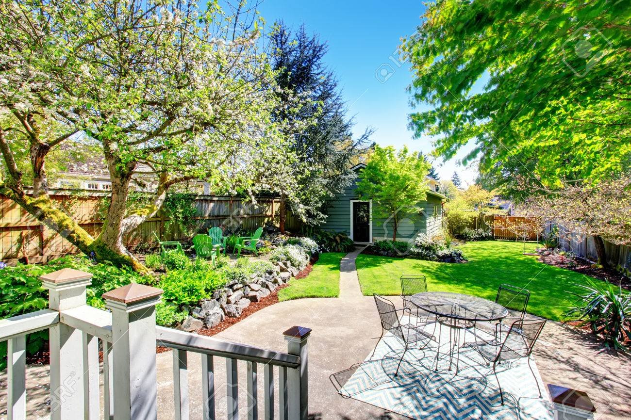 Beautiful backyard garden with two patio areas, shed and blooming trees. - 59956191