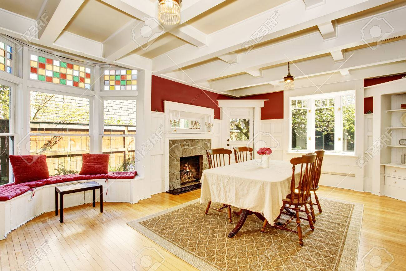 Luminoso comedor de paredes rojas y adornos de madera blanca. También  chimenea con decoración en piedra y sala de estar con una amplia ventana.