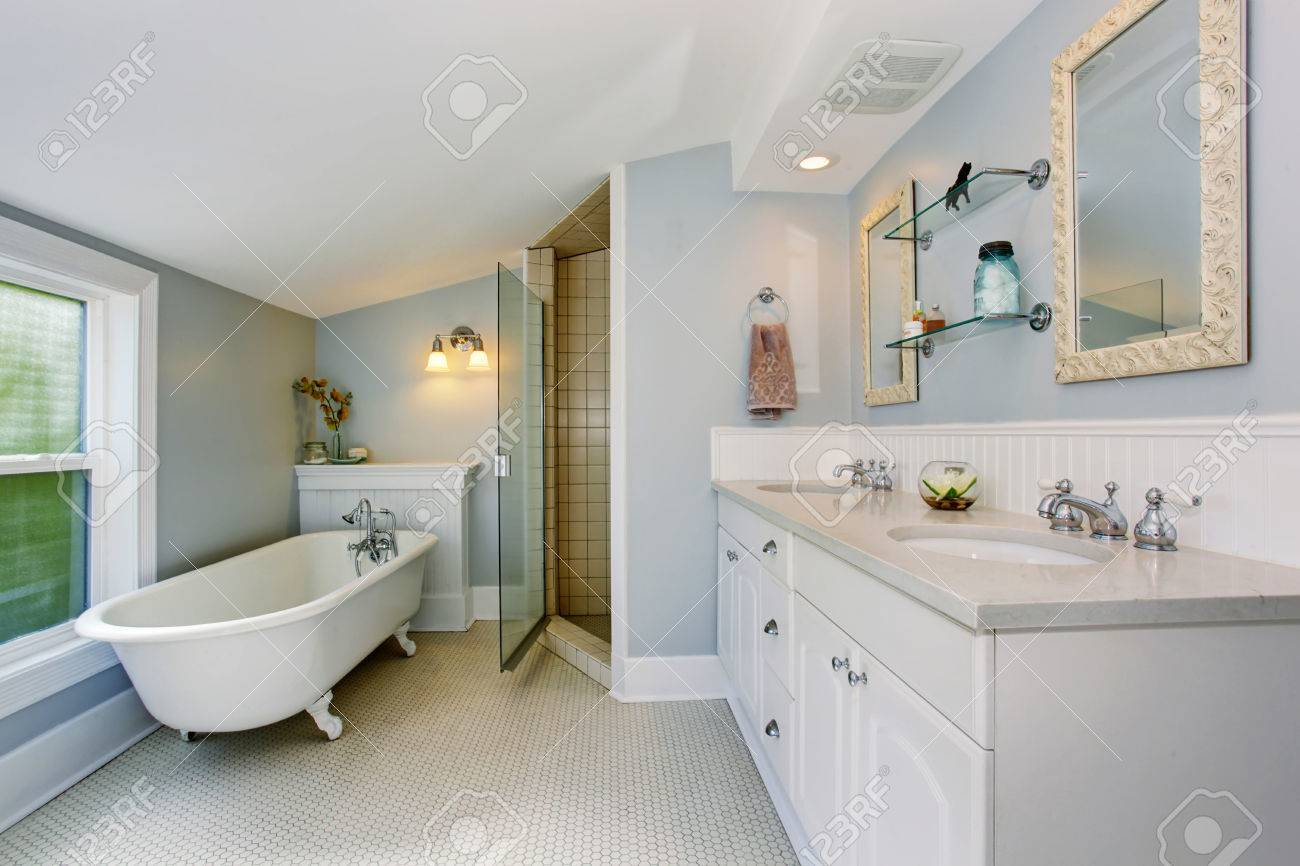 Cuarto de baño elegante en tonos azul pastel, con tina de baño blanca,  armarios y ducha.