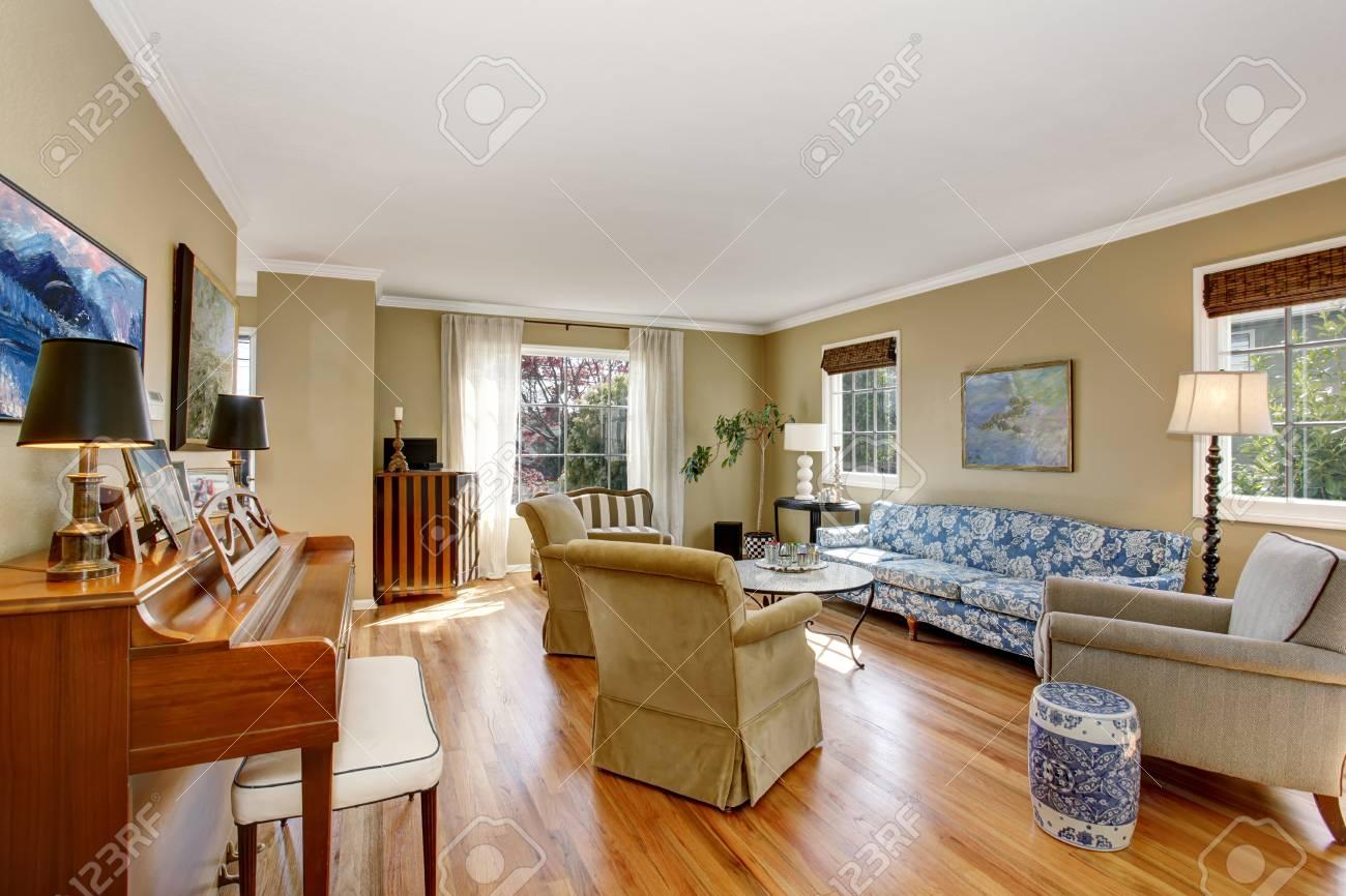 Intérieur de salon américain classique avec piano, canapé bleu et plancher  de bois franc. Certaines photos sur les murs beiges, les lampes et le pot  ...
