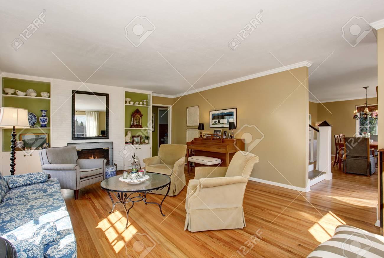 Intérieur de salon américain avec canapé classique et plancher de bois  franc. Vue de la salle à manger.