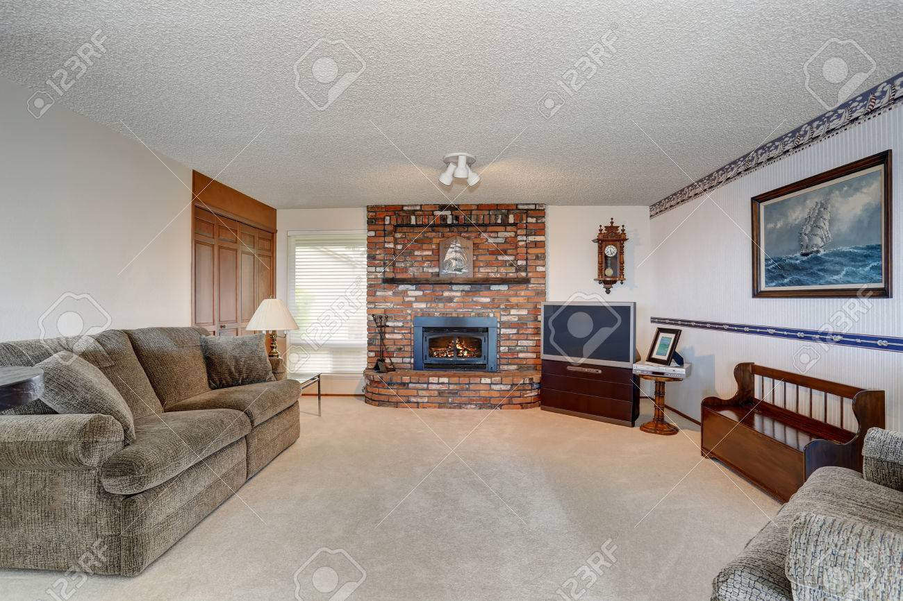 American Living Room. Cozy American living room with gray sofa  carpet floor and brick fireplace Stock Photo Living Room With Gray Sofa Carpet Floor And Brick