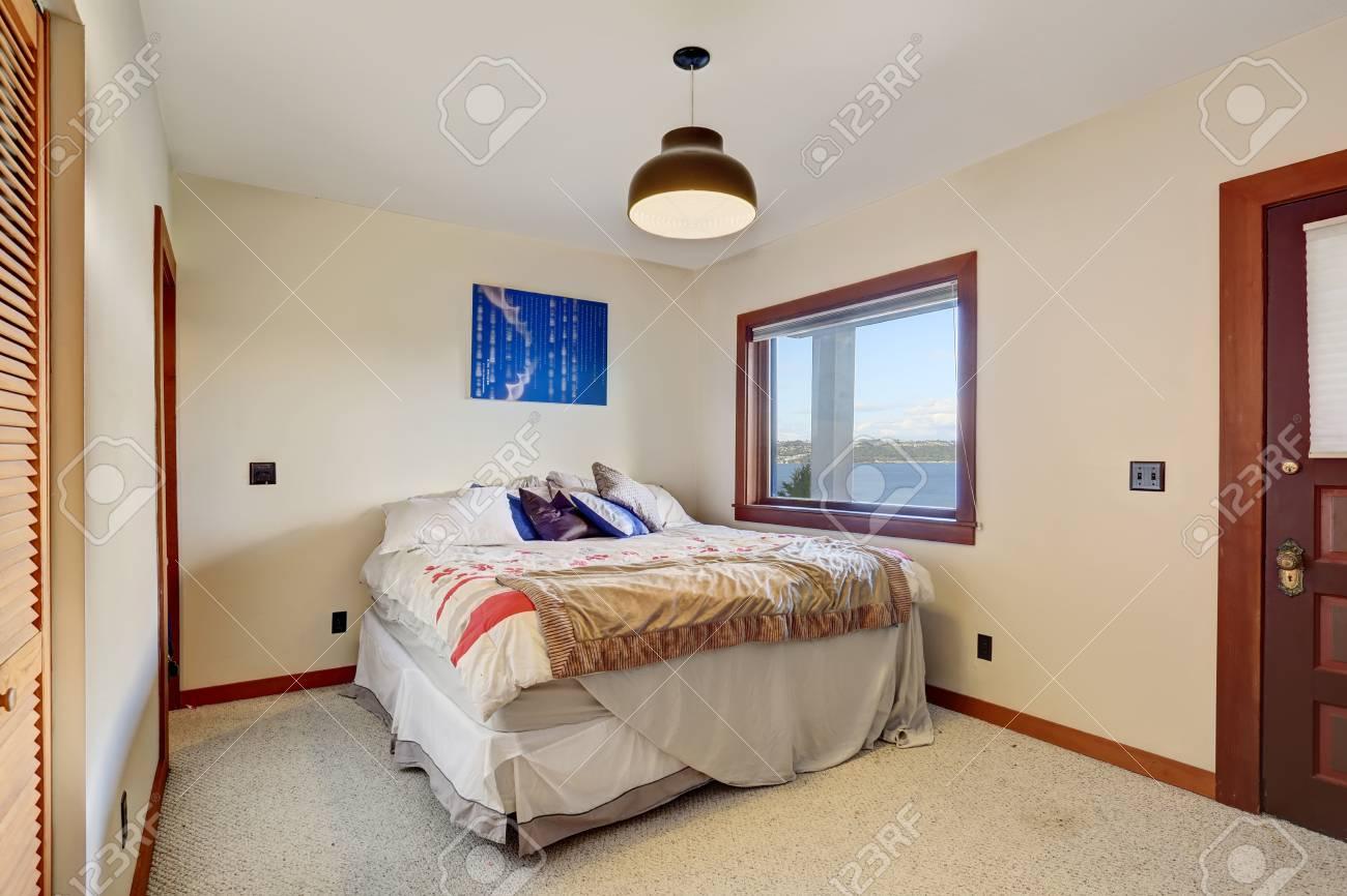 Camera da letto semplice con un letto, pavimento in moquette e pareti  bianche con finiture in marrone