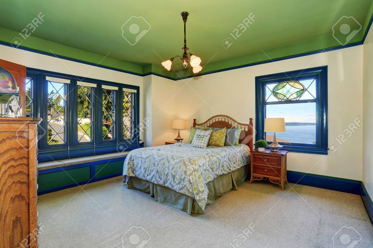 Adorable antique bedroom interior with green ceiling and blue..