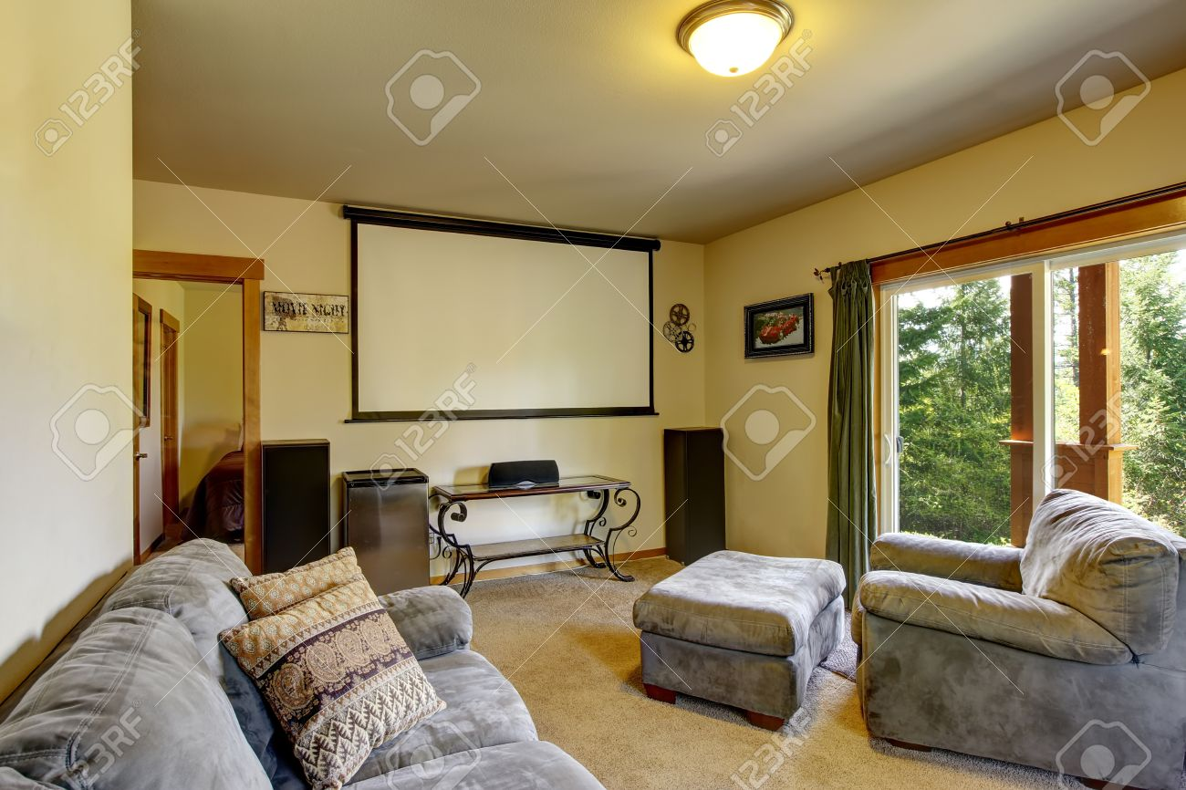 Cinema Room In American House With Projector Screen On The Wall, Furnished  With Comfortable Gray