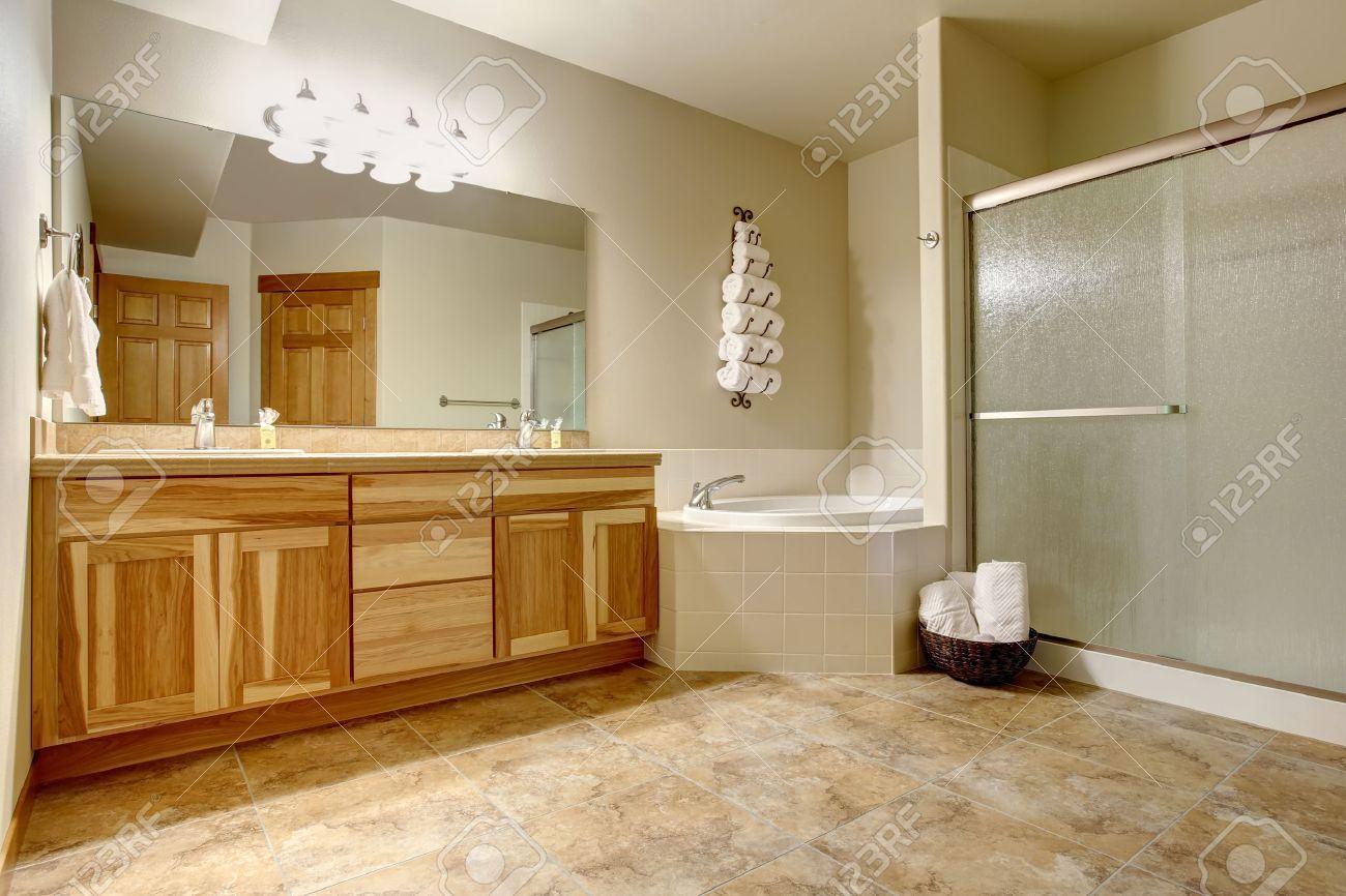 Cuarto de baño elegante en tonos suaves con gabinetes de madera y mármol  suelo de baldosas. Bañera blanca con la franja de azulejos en la esquina y  ...