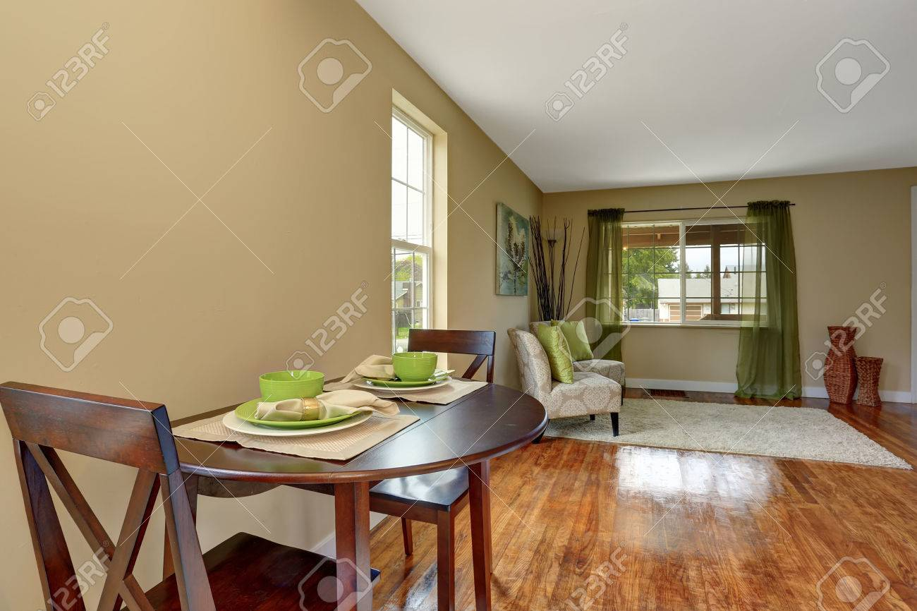 Cozy Beige Sitting Room With Shiny Hardwood Floor Connected With Dining Area.  Furnished With Elegant