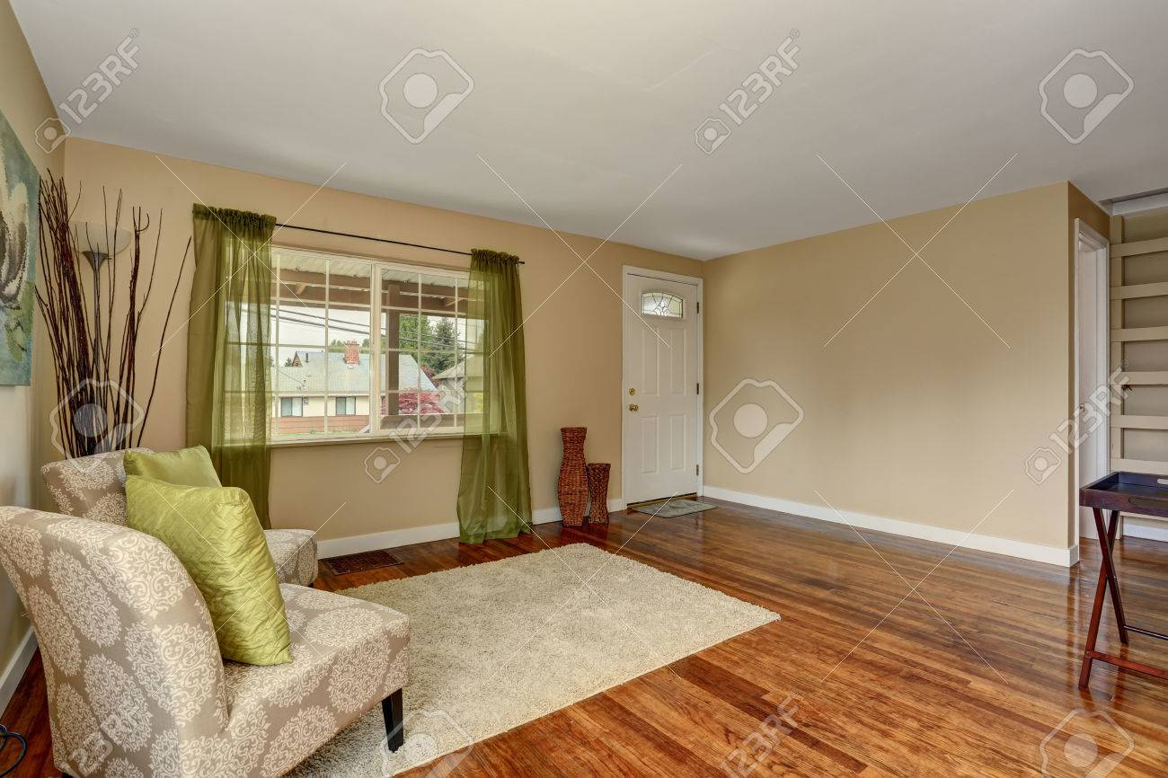 Cozy Beige Sitting Room With Shiny Hardwood Floor And Green Curtain