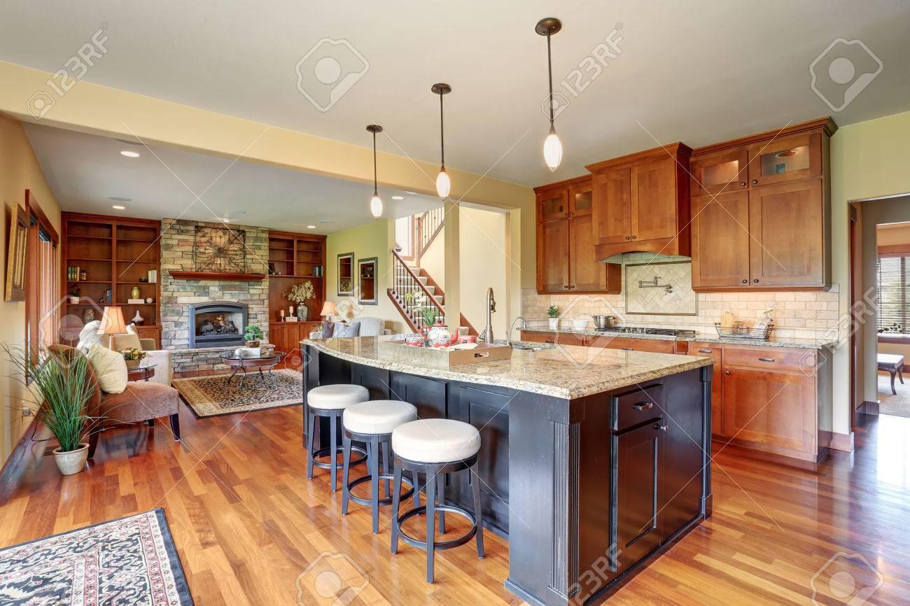 Coin Chambre Dans Petit Salon petit coin cuisine avec plan d'étage ouvert, vue sur le salon. cuisine  chambre dispose d'îlot de cuisine noir avec comptoir en granit et tabourets