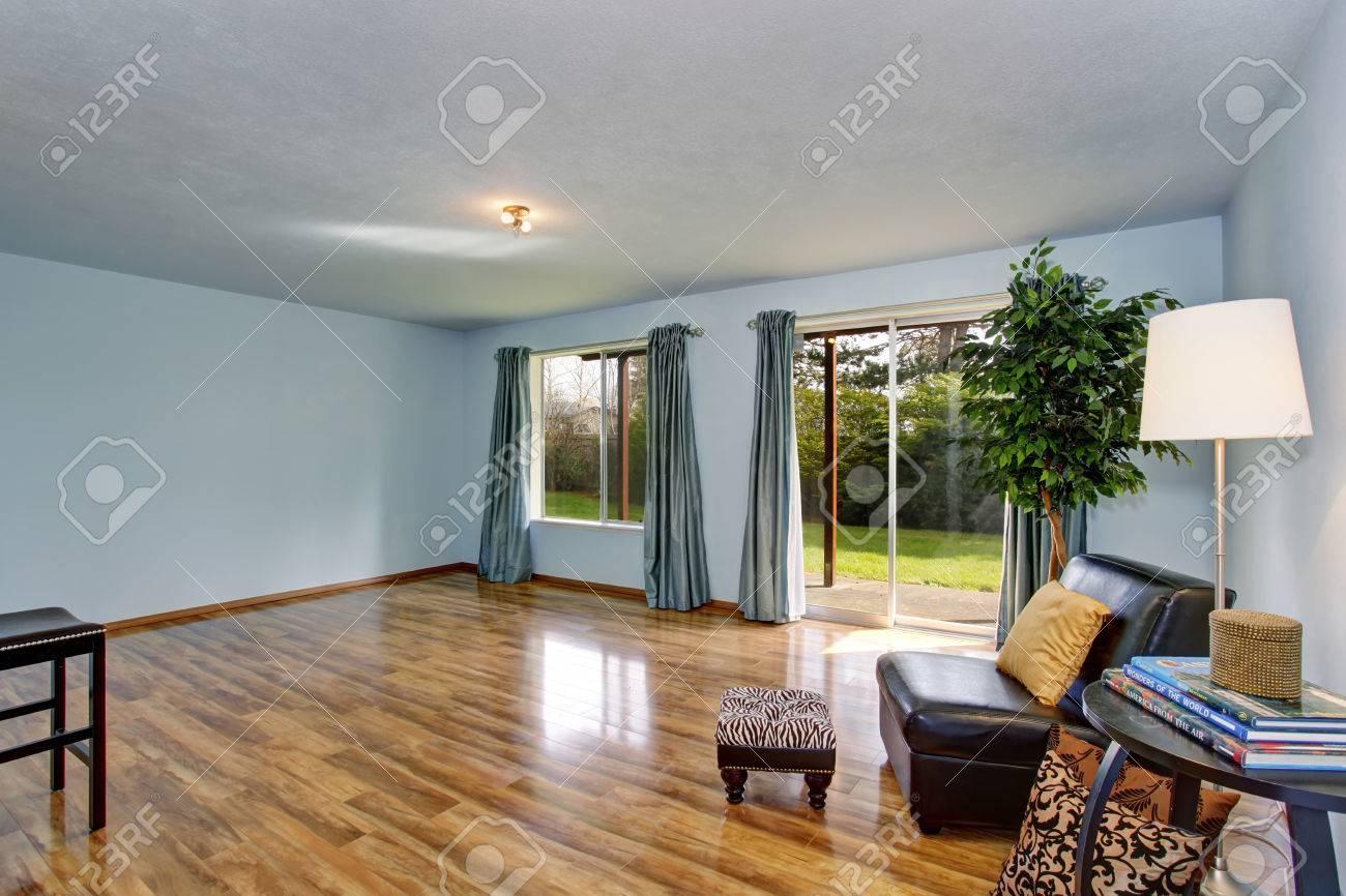 Unfinished intérieur du salon avec des murs bleus et rideaux bleus.  Plancher de bois franc et une chaise en cuir noir