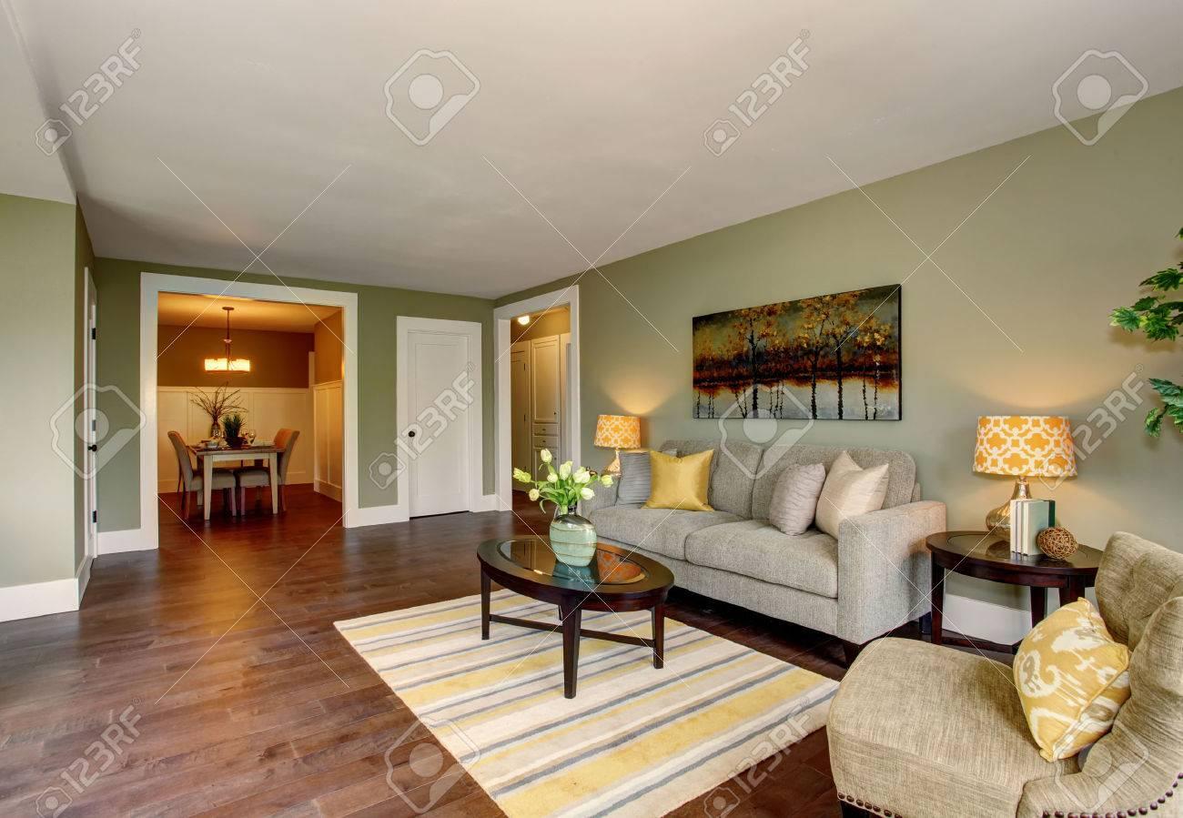 Viviendo entre habitación con paredes verdes piso y alfombra de madera  dura. Comedor