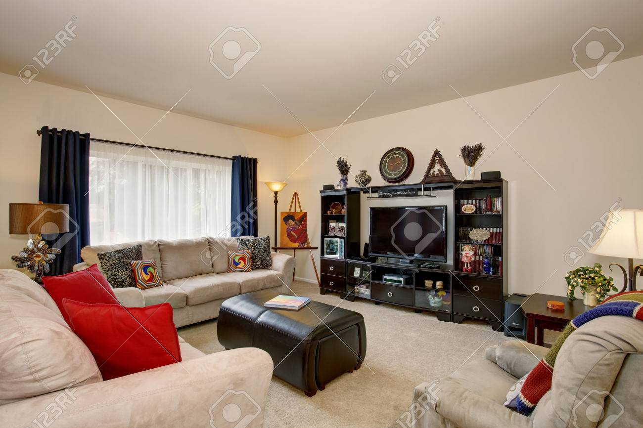Cozy living room with beige sofa set and red pillows and black..