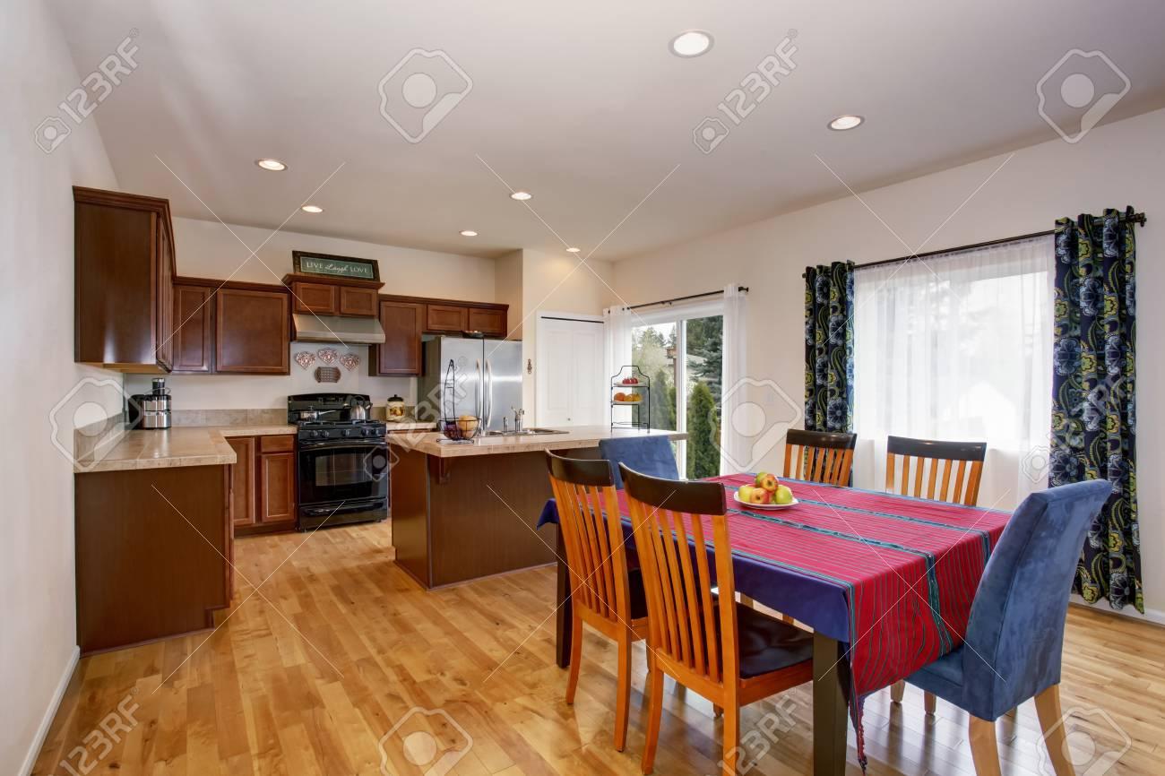 Luminosa cucina e sala da pranzo interna con pareti bianche, tende colorate  e pavimento in legno.