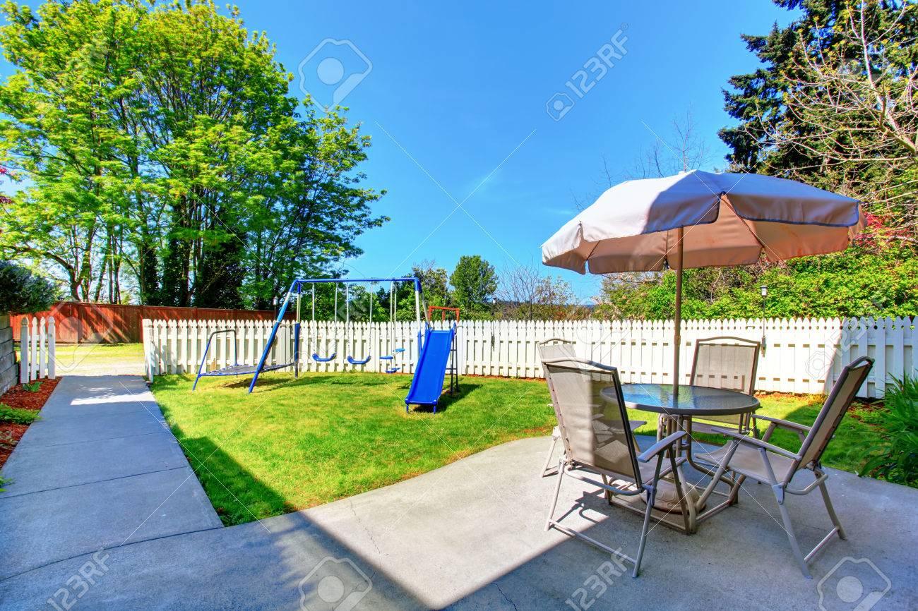 Maison Pour Enfant Exterieur extérieur maison. petite cour arrière clôturée avec sol en béton terrasse  et jeux pour enfants.