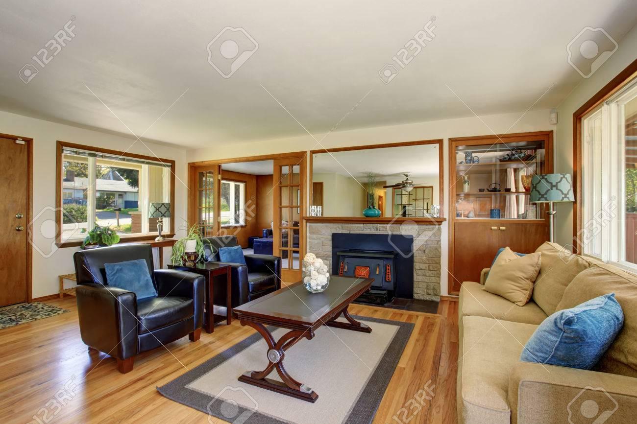 Intérieur classique de salon américain avec des fauteuils en cuir noir et  cheminée. Plancher de bois franc, plafond blanc et garniture brun.