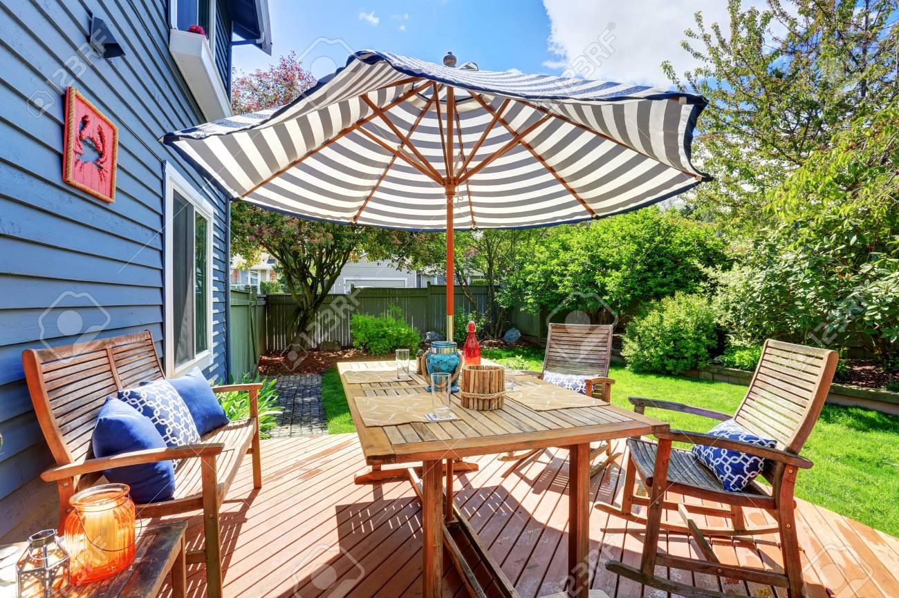 Pont de débrayage en bois dans le jardin à l\'arrière de la maison bleue de  parement. Meublé avec patio set de table avec parasol