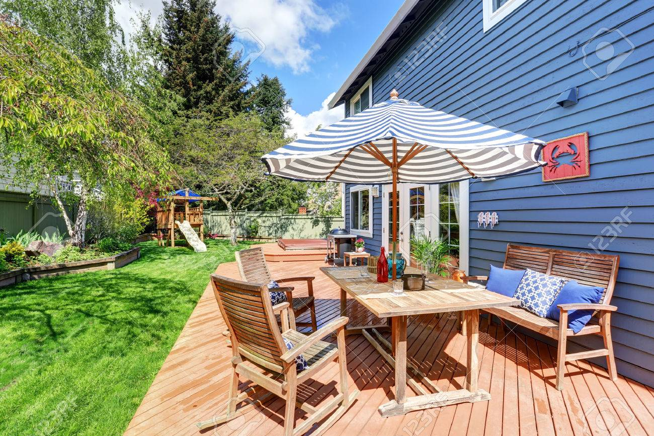 Pont de débrayage en bois dans le jardin à l\'arrière de la maison bleue de  parement. Meublé avec table de patio fixé avec un parasol. Aussi les ...