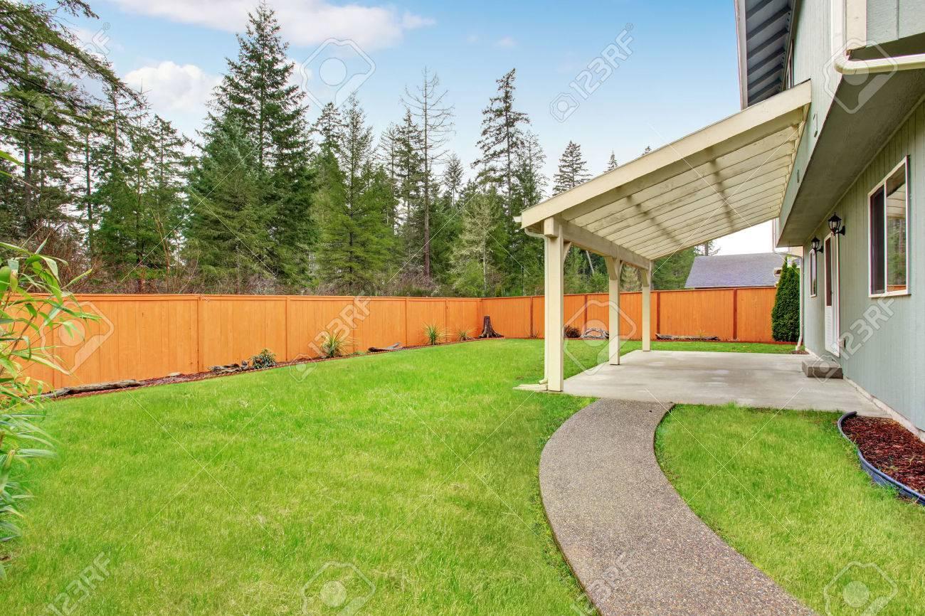 Terrasse couverte d\'arrière-cour avec sol en béton. cour brun clôturé et  pelouse bien entretenue autour
